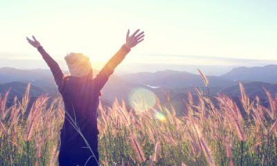 happy woman atop mountain meadow enjoying sunrise